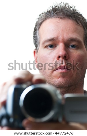 A man shooting with a video camera, focus on the man's face, isolated on white. - stock photo