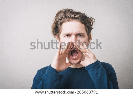 A man shouts with his hands near his mouth. On a gray background. - stock photo