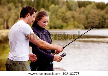 A man showing a woman how to fish
