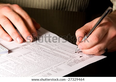 A man signing 1040 tax forms