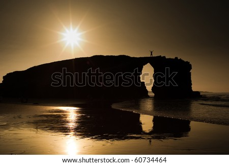 A man silhouette over a big rock in a beach at sunset. Reflection of the rock is clearly visible on the sand.