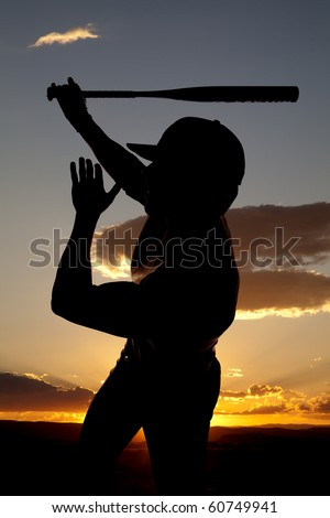 A man silhouetted by the sunset is finishing the swing of his bat - stock photo