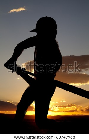 A man silhouetted by the sunset is just beginning to swing his bat. - stock photo
