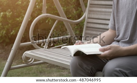 A Man sit on the swing and reading a book for banner presentation,vintage tone.