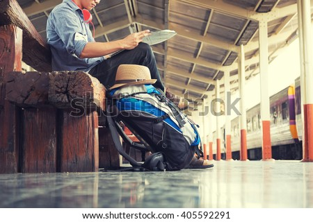 A man sit with map. travel bag at the train station. - stock photo