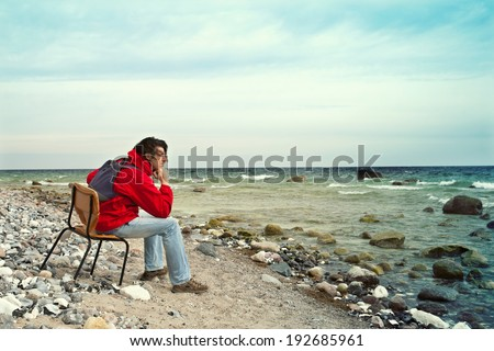 a man sits on the old chair by the sea