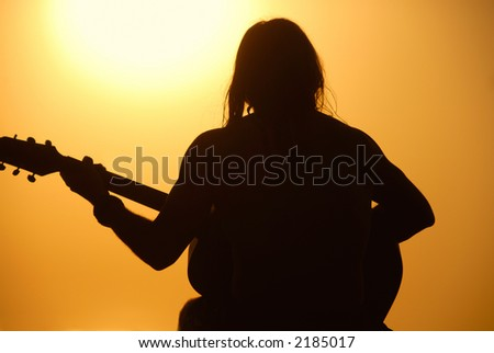 A man sits playing his guitar silhouetted against a bright setting sun. - stock photo