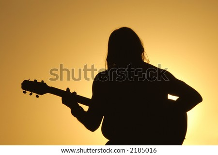 A man sits silhouetted against a bright setting sun playing his guitar.