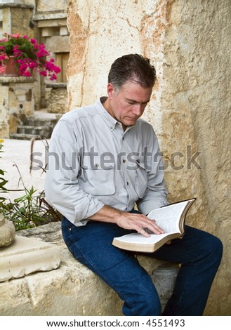 A man sitting and reading what appears to be a bible. - stock photo