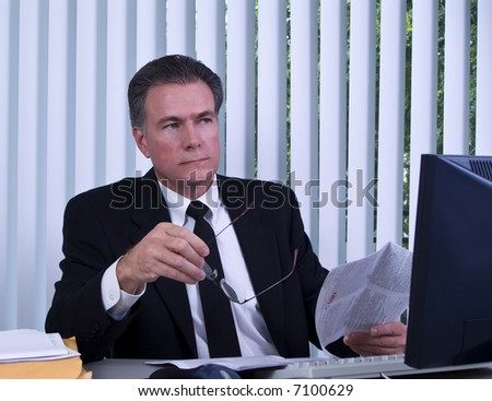 A man sitting at a computer as if pondering the content of the document he is reviewing. - stock photo