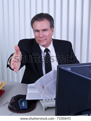 A man sitting at a desk with a legal size document exteding his hand as if to welcome someone.