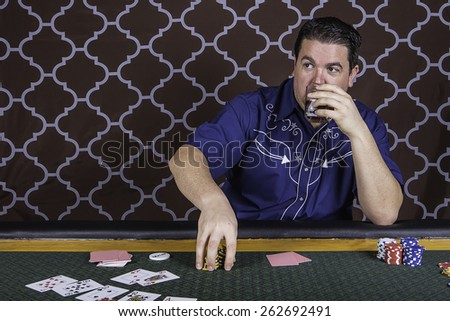 A man sitting at a poker table gambling playing cards against a brown background - stock photo