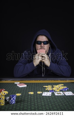 A man sitting at a poker table wearing a hoodie gambling playing cards against a black background - stock photo
