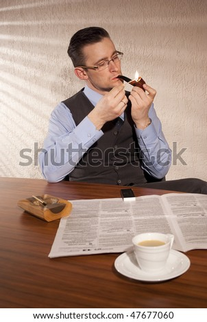 A man sitting at the table for morning coffee, smoking pipe and read the newspaper. Filtering light from a window. - stock photo