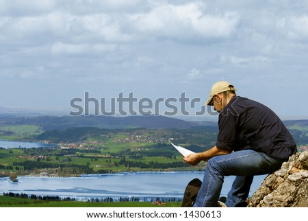 A man sitting at the top of the rock - stock photo
