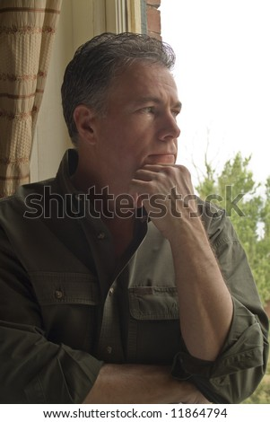 A man sitting by a window, with an anxious or worried look on his face. - stock photo