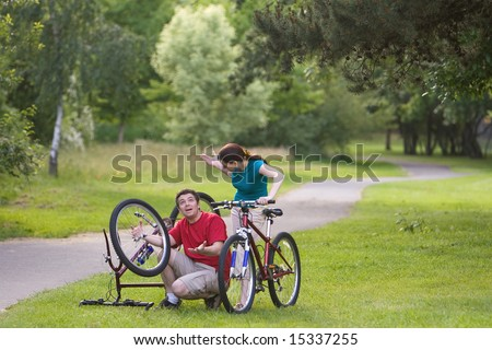 A man, sitting down, attempts to fix his bicycle, while it is upside-down and explaining it to the woman. The woman stands behind him, watching. - horizontally framed - stock photo
