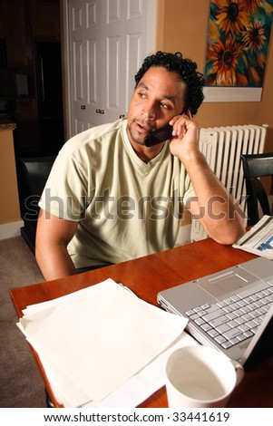 A man sitting down in front of his computer talking on the telephone