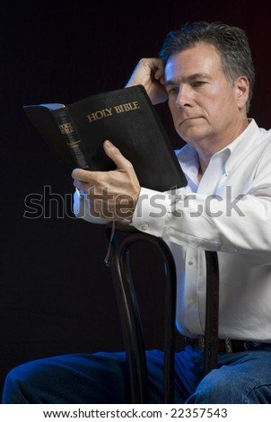 A man sitting in a dark room reading a bible, side lit with blue gel for mood. - stock photo