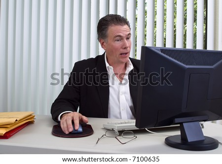 A man sitting in front of a computer with a very surprised expression on his face.