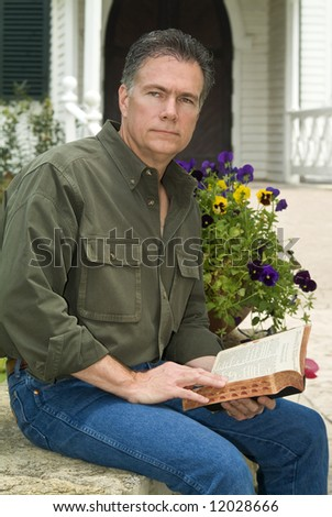 A man sitting in front of a country church holding a bible in his hand with a pensive look on his face. - stock photo