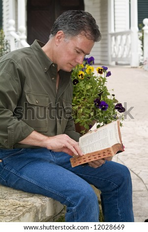 A man sitting in front of the entrance to a church building studying from his bible.