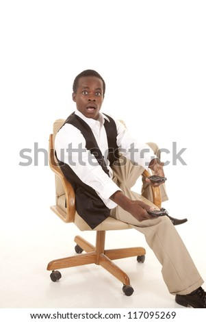 A man sitting in his chair with two remotes with a shocked expression his face at what he just saw. - stock photo