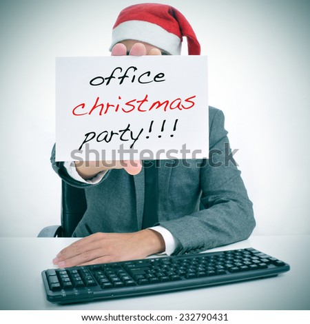 a man sitting in his desk with a santa hat holding a signboard with the text office christmas party written in it