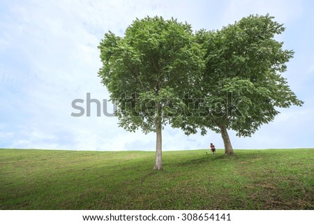 A man sitting lonely under the couple of tree - stock photo
