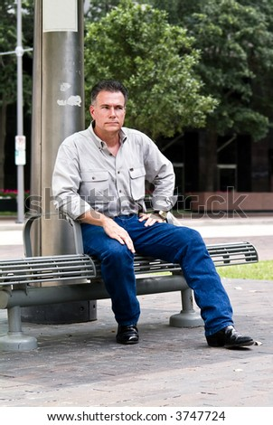 A man sitting on a bench at a downtown bus stop. - stock photo
