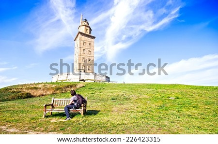 A man sitting on a bench looking The Hercules tower in La Coruna, Galicia, Spain, UNESCO - stock photo