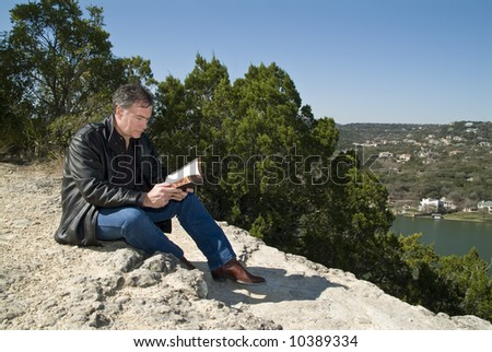 A man sitting on a rocky ledge reading a bible. - stock photo
