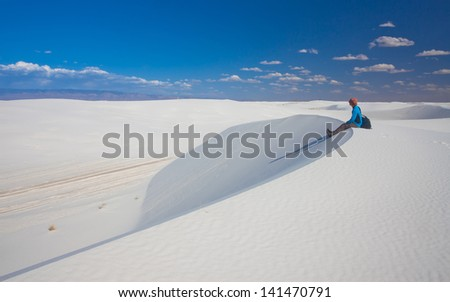 A man sitting on a sand dune in White Sands National Monument, New Mexico, USA - stock photo
