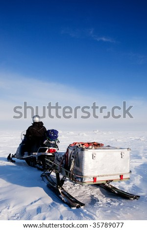 A man sitting on a snowmobile on a barren snow landscape