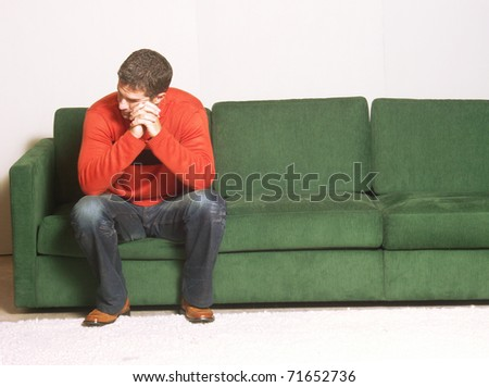 A man sitting on a sofa. - stock photo