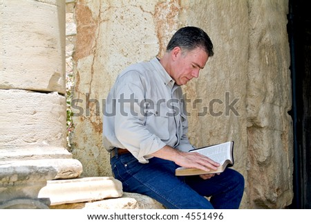 A man sitting on a stone wall reading what appears to be a bible. - stock photo