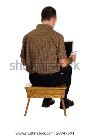 A man sitting on a stool doing some online shopping with a credit card