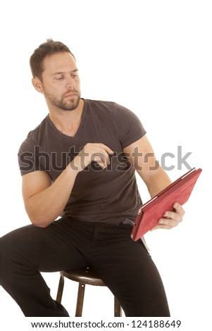 a man sitting on a stool looking at his electronic tablet with a serious expression on his face. - stock photo