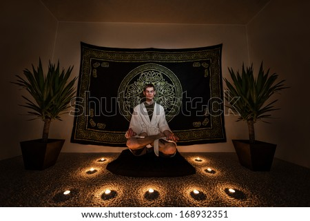 A man sitting on a zafu cushion with in a white robe with his eyes closed doing a  meditation ritual. There are plants, candles, and a tapestry behind him on the wall.  - stock photo