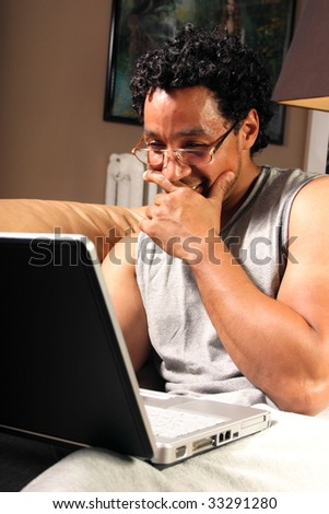 A man sitting on his couch chatting on a laptop laughing