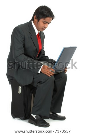 a man sitting on his luggage over a white background - stock photo