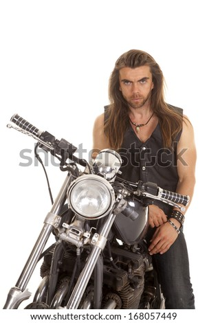 a man sitting on his motorcycle with a serious expression. - stock photo
