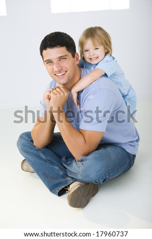 A man sitting on the floor with cross-legged and his daughter hugging him. They're smiling and looking at camera. - stock photo