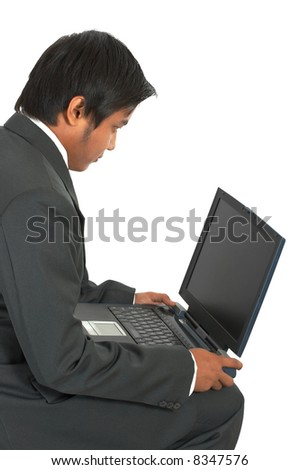 a man sitting while working on his laptop computer
