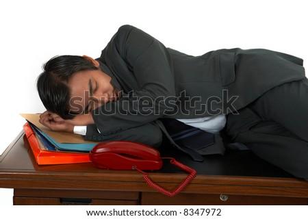 a man sleeping on his office desk - stock photo