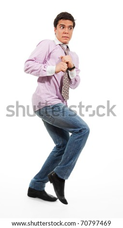 A man slinking with afraid face expression, wearing jeans, shirt and tie, isolated on white - stock photo