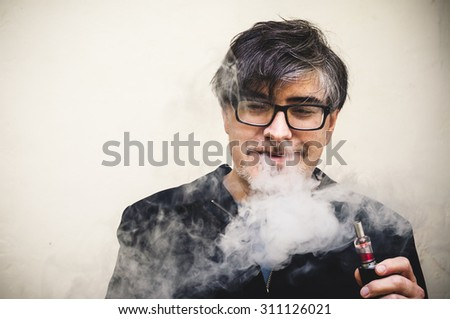 A man smiles while vaping/using an electronic cigarette.