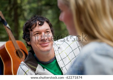A man smiling at a woman with a guitar in the background - stock photo