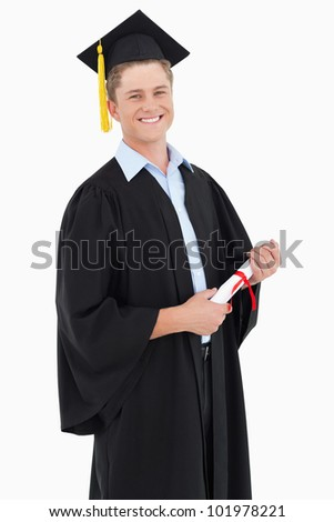 A man smiling with his degree as he looks at the camera