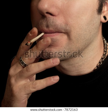 A man smoking a marijuana joint. - stock photo